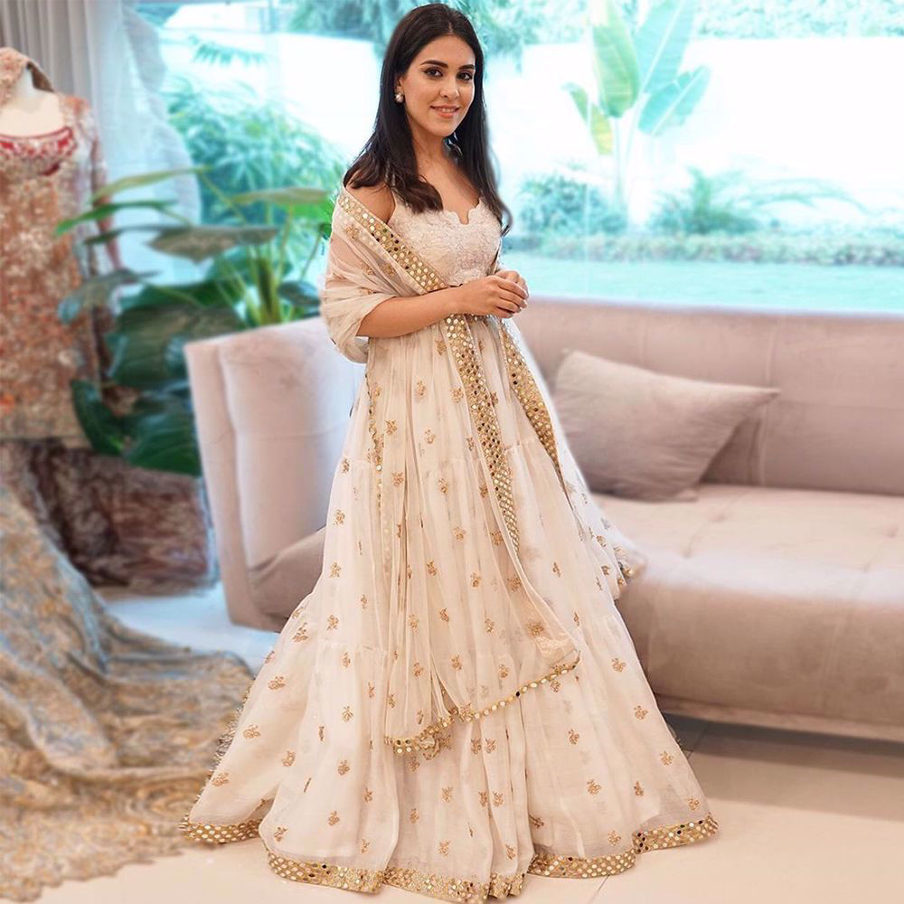 Picture of Aymen Hikmat experiences royalty wearing a beautiful white lehnga choli, with hues of gold, intricately embroidered and meticulously detailed with mirror work highlighting the exquisite craftsmanship of our artisans