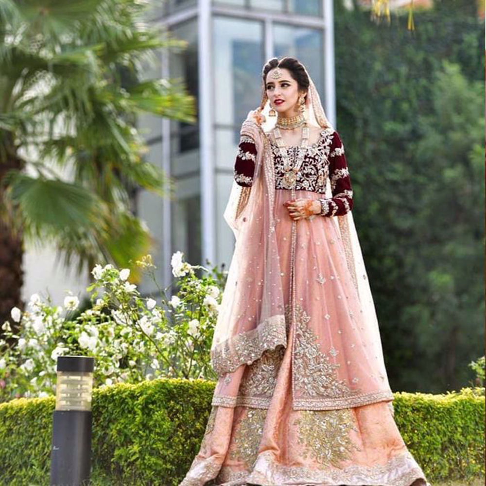 Picture of Absolutely head over heels in love with our bride carrying our effeminate coral Meherma outfit with a blush maroon velvet bodice